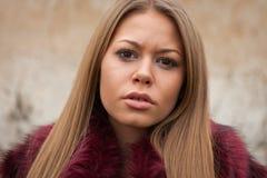 Melankolisk ung flicka med det röda pälslaget Arkivfoto