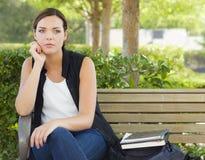 Melankoliskt ungt sammanträde för vuxen kvinna på bänk därefter Arkivfoto