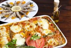 Melanzane alla Parmigiana och Marinated sardiner Arkivbild