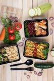 Melanzane fritte in contenitore con le ali di pollo arrostite e le verdure crude su fondo rustico, sul pomodoro ciliegia e sui mi fotografie stock libere da diritti