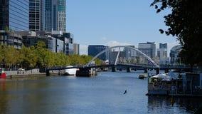 Melbourne, Austrália - 6 de abril de 2018: Ponte do arco-íris e rio de Yarra cercado por arranha-céus Imagem de Stock Royalty Free
