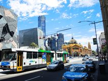 Light rail tram running through a street near iconic Flinders Street railway station. royalty free stock photo