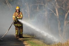 Fire fighter spraying water on a bush fire in an suburban area of Knox City in Melbourne east. Melbourne, Australia - April 13, 2018: Fire fighter spraying Stock Image
