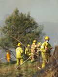 Fire fighters spraying water on a bush fire in an suburban area of Knox City in Melbourne east. Melbourne, Australia - April 13, 2018: Fire fighters spraying Stock Images