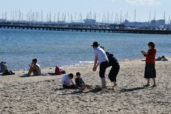 MELBOURNE, AUSTRALIA - AUGUST 14, 2017 - People relaxing on st. Kilda the beach. MELBOURNE, AUSTRALIA - AUGUST 14, 2017 - located 6 kilometres south from the stock photo