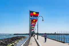 St Kilda Pier with rows of national flags with Australian Aborig Stock Photography