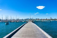 Young people on St. Kilda pier with Melbourne cityscape on the b. Melbourne, Australia - December 7, 2016: Young people on St. Kilda pier with Melbourne Royalty Free Stock Images
