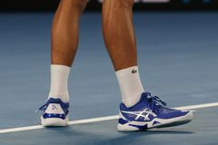 Grand Slam champion Novak Djokovic of Serbia wears custom Asis tennis shoes during his final match at 2019 Australian Open. MELBOURNE, AUSTRALIA - JANUARY 27 stock photo