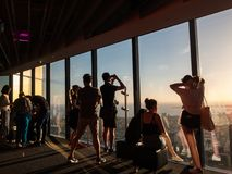 Tourists looking out the Eureka Skydeck windows in Melbourne, Australia. Melbourne, Australia - January 16, 2018: tourists looking out the windows of Eureka Royalty Free Stock Images