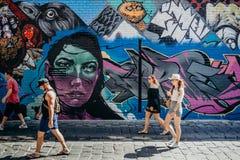 MELBOURNE, AUSTRALIA - March 12, 2017: People walking along the street watching graffiti walls in Melbourne, Australia. Stock Photo