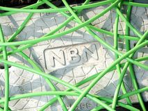 Green NBN fibre optic cable in a unstructured mess over a pit with a concrete man hole cover displaying the NBN word mark. Melbourne, Australia - May 14, 2018 stock image