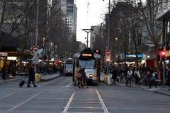 MELBOURNE AUSTRALIEN, AUGUSTI 16 2017 - Melbourne gator trafikerar, lokalen och turisten på solnedgången fotografering för bildbyråer