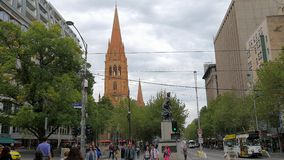Melbourne city center. MELBOURNE, AUSTRALIA - MARCH 16, 2015: Busy Swanston street in Melbourne and Cathedral of Saint Paul in background stock footage