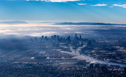 Melbourne horisont med skyskrapor som dyker upp från morgondimman Arkivbild