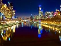 Melbourne på natten som ser ner yarrafloden Arkivbild