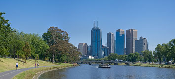 Melbourne skyline along the Yarra River. Walkers on the path on the left and a river ferry on the right Royalty Free Stock Photo