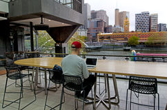 Melbourne Southbank - Victoria. MELBOURNE - APR 11, 2014:Man work on laptop at  Southgate Shopping Complex in Melbourne Southbank.It is one of the primary Royalty Free Stock Photography