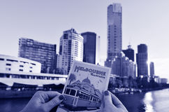 Melbourne Southbank - Victoria. MELBOURNE - APR 14, 2014: Womans hand hold a postcard against Melbourne Southbank skyline.It is one of the primary business Royalty Free Stock Photography