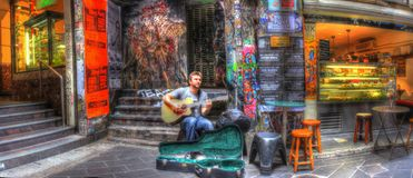 Melbourne street busker. Young man busking for money playing guitar in graffiti coveted lane in Melbourne, Australia Stock Images