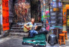 Melbourne street busker. Young man busking for money playing guitar in graffiti coveted lane in Melbourne, Australia Royalty Free Stock Photo