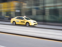 Melbourne Taxi and Tramline. Pan shot of a Melbourne Taxi zooming past Southern Cross Station Royalty Free Stock Image