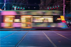 Melbourne tram travelling past at night time. Motion blur of a tram or light rail carriage careening past on the street with public transport commuters on board stock photo