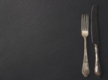 Melchior spoon and fork on the black stone background. Top view Stock Images