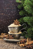 Melchior vintage cups with cane sugar, anise stars, Indian Indian cinnamon sticks on an aged wooden background. Surrounded by spruce spruce branches. Toned Royalty Free Stock Photos