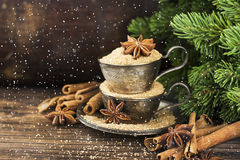 Melchior vintage cups with cane sugar, anise stars, Indian Indian cinnamon sticks on an aged wooden background. Surrounded by spruce spruce branches. Toned Stock Photo
