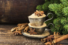 Melchior vintage cups with cane sugar, anise stars, Indian Indian cinnamon sticks on an aged wooden background. Surrounded by spruce spruce branches. Toned Royalty Free Stock Photo