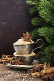 Melchior vintage cups with cane sugar, anise stars, Indian Indian cinnamon sticks on an aged wooden background. Surrounded by spruce spruce branches. Toned Stock Images