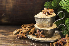 Melchior vintage cups with cane sugar, anise stars, Indian Indian cinnamon sticks on an aged wooden background. Surrounded by spruce spruce branches. Toned Stock Photography