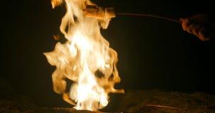 Melcocha de la carne asada del hombre en el fuego