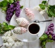Melcocha, una taza de café y lila Imagen de archivo