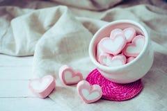 Melcochas de la forma del corazón en la taza blanca en el fondo de madera, dulce Imagen de archivo libre de regalías