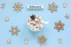 Melcochas del cacao de la taza de febrero del calendario y copos de nieve de madera grandes fotografía de archivo libre de regalías