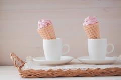 Melcochas o céfiro rosadas en las tazas blancas en el fondo de madera Imagenes de archivo