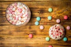 Melcochas rosadas azules de moda, torta dulce, caramelos en la tabla de madera Imagen de archivo libre de regalías