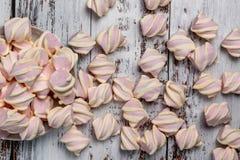 Melcochas rosadas con los rizos amarillos, en fondo de madera ligero Vertido de la placa fotografía de archivo