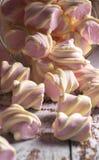 Melcochas rosadas con los rizos blancos que consiguen bastante sue?o con un envase transparente en fondo de madera ligero imagen de archivo