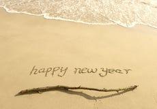 Meldung des glücklichen neuen Jahres auf dem Sand Lizenzfreie Stockbilder