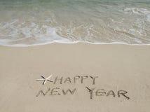 Meldung des glücklichen neuen Jahres auf dem Sand Lizenzfreie Stockfotografie