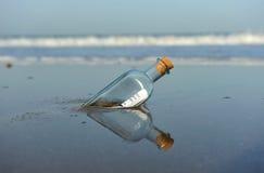 Meldung in einer Flasche auf dem Strand Stockbilder