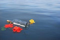 Meldung in einer Flasche, die mit Blumen schwimmt Stockbilder