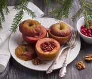 Mele al forno farcite con i mirtilli rossi, le noci ed il miele con cannella Fotografia Stock