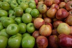 Mele brillanti fresche verdi ed arancio con un fondo solido, frutta fresca sul mercato Immagine Stock Libera da Diritti