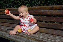 Mele di lancio di una neonata alla terra Immagini Stock