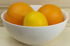 Mele ed arance naturali succose fresche in un piatto bianco brillante su fondo di legno Fotografia Stock Libera da Diritti