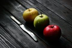 Mele gialle verdi rosse in una fila diagonale con le gocce di acqua del coltello sulla tavola di legno nera, luce posteriore Fotografia Stock Libera da Diritti