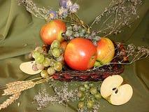 Mele mature con l'uva in un canestro fotografia stock
